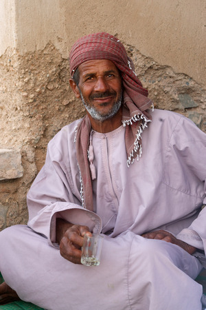 headcloth: A bearded Omani man, wearing a traditional headcloth, enjoying a glass of tea at the castle in the market town of As Suwayq in the Sultanate of Oman.
