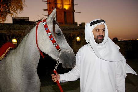 hombre arabe: Un hombre árabe lleva su caballo árabe gris en la puesta del sol en Dubai. Lámparas de parafina tradicionales y un Windtower se pueden ver en el fondo. Editorial