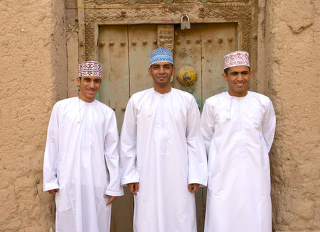 BIRKAT AL MOUZ, OMAN ? FEBRUARY 2, 2008: Three young Omani men in traditional dress at the ruins of Birkat Al Mouz in the Nizwa area of the Sultanate of Oman.