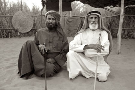 gcc: A monochrome image of two Arab men at their camp near Dubai. The older man on the right, Humaid Ali Alrezi, a poet, is blind. Editorial
