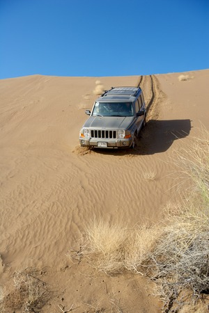 A Dubai-registered Jeep Commander 4x4 vehicle negotiates a steep dune while driving offroad in the interior of the Sultanate of Oman. Editorial