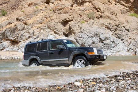 Wadi: A Dubai-registered Jeep Commander 4x4 vehicle negotiates a river in the desert interior of the Sultanate of Oman.