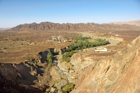 Wadi: Wadi Madbah, with its traditional irrigation canal (aflaj) and date palms, runs past a small hamlet in the desert interior of the Sultanate of Oman. Stock Photo