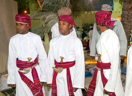 muscat: Three young Omani men in traditional dress, with khanjars (Arabian daggers), at a cultural festival in Muscat, in the Sultanate of Oman. Editorial