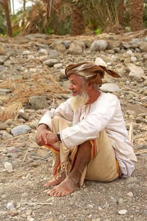 woollen: An Omani man, wearing a muzzar (traditional woollen turban), relaxes in a wadi below his date plantation in the rural interior of the Sultanate of Oman.
