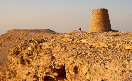 dramatically: One of the Beehive Tombs of Bat perched dramatically atop a rocky ridge in Oman. The tombs are among the most unique ensemble of 40005000 yearold burial monuments towers and remains of settlement in the Arabian Peninsula a Stock Photo