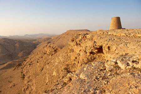 stonemasonry: One of the Beehive Tombs of Bat perched dramatically atop a rocky ridge in Oman. The tombs are among the most unique ensemble of 40005000 yearold burial monuments towers and remains of settlement in the Arabian Peninsula Stock Photo