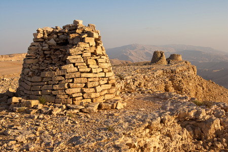 dramatically: Lined up dramatically atop a rocky ridge the Beehive Tombs of Bat in Oman are among the most unique ensemble of 40005000 yearold burial monuments towers and remains of settlement in the Arabian Peninsula.  Stock Photo