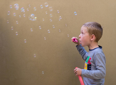 young boys: A young boy blowing bubbles against a beige wall background. Stock Photo