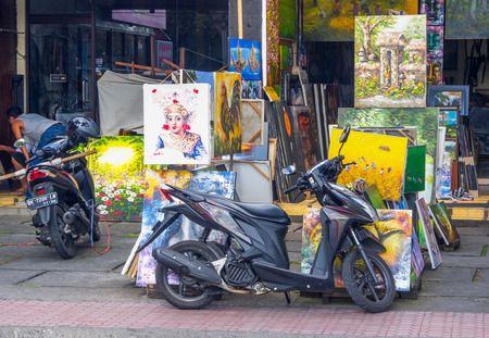 ubud: UBUD, BALI OCTOBER 12, 2016: Colorful paintings and scooters outside an artists studio in Ubud, in Central Bali, Indonesia.