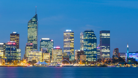 PERTH, WESTERN AUSTRALIA - APRIL 7, 2016: Dusk falls over the city of Perth, the capital of Western Australia. The Swan River can be seen in the foreground.