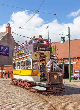 durham: BEAMISH, UK - JULY 27, 2012: Newcastle 114, a tram built in 1901, trundles down the high street of the Edwardian town that forms part of Beamish Museum in County Durham, England. Beamish is a world-famous open-air museum that tells the story of life in  Editorial