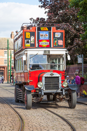 durham: BEAMISH, UK - JULY 27, 2012: An old bus at a bus stop in the high street of the Edwardian town that forms part of Beamish Museum in County Durham, England. Beamish is a world-famous open-air museum that tells the story of life in North-East England in Geo