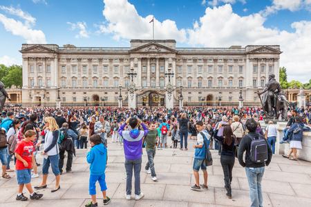 LONDON, UK - JULY 11, 2012:  Crowds gather outside Buckingham Palace to watch the changing of the guard ceremony.