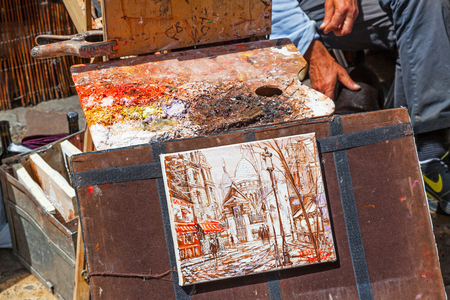 An artists colorful palette and painting, in autumnal shades of orange, red and brown, in Montmartre in Paris.