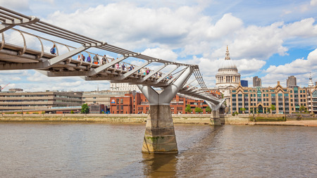 LONDON, UNITED KINGDOM – JUNE 12, 2012: Pedestrians on the London Millennium Footbridge, a steel suspension bridge crossing the River Thames, with St Pauls Cathedral in the background.