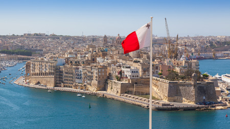 Senglea fortified city and Fort Saint Michael across Grand Harbour from Valletta, Malta. The photo incorporates a Maltese flag. Stock Photo