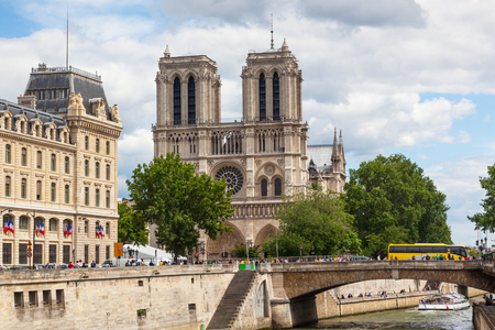 Unidentified people gather at Notre Dame Cathedral in Paris, France, with the River Seine in the foreground. Editorial