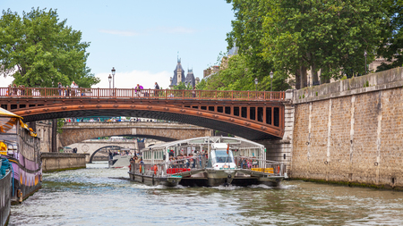 PARIS, FRANCE - JUNE 8, 2012: A modern pleasure boat laden with tourists passing under a  bridge on the River Seine in Paris. Editorial