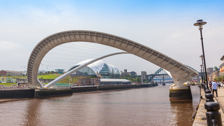 NEWCASTLE UPON TYNE, ENGLAND - JULY 5, 2012: A view of Gateshead Millennium Bridge, which crosses the  River Tyne, in Newcastle Upon Tyne in the North East of England. The Sage Gateshead building can be seen in the background.