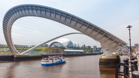 NEWCASTLE UPON TYNE, ENGLAND - JULY 5, 2012: A view of Gateshead Millennium Bridge, which crosses the  River Tyne, in Newcastle Upon Tyne in the North East of England. The modern Sage Gateshead building can be seen in the background.