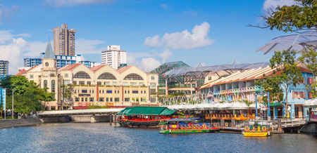 Colorful boats moored at Clarke Quay on the Singapore River with Riverside Point in the background