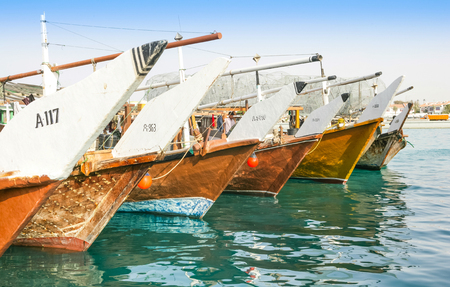 Traditional wooden fishing dhows berthed in the Dhow Harbour in Abu Dhabi, the capital city of the UAE.