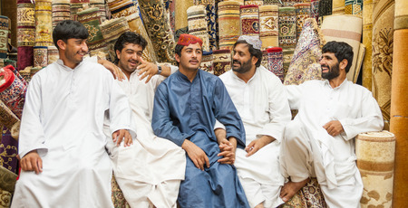 A group of unidentified male Pakistani salesmen at the carpet souk in Abu Dhabi, the capital city of the United Arab Emirates.