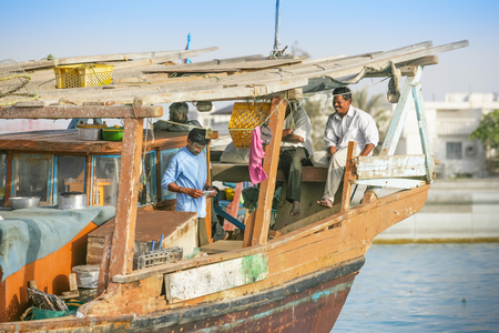 Unidentified crewmen relaxing aboard a traditional wooden fishing dhow berthed in the Dhow Harbour in Abu Dhabi, the capital city of the UAE. Editorial