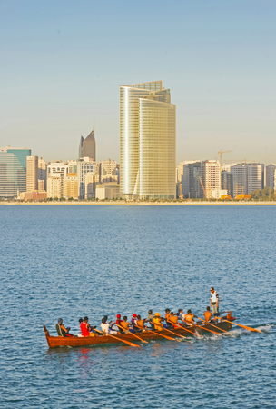 Arab oarsmen rowing a traditional longboat in front of the Abu Dhabi Corniche in the late afternoon. Editorial