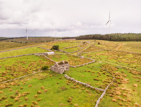 An aerial view of  wind turbines and an abandoned farm house between the towns of Spiddal and Moycullen in County Galway, Ireland 免版税图像