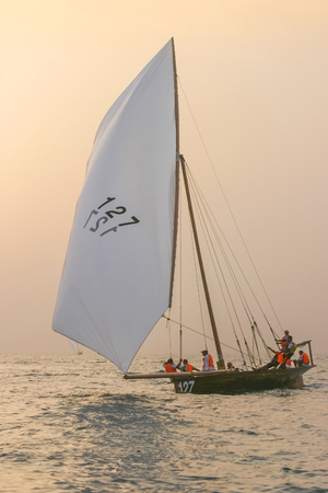 DUBAI, UAE - DECEMBER 16, 2004: A traditional racing dhow approaching the finishing line off Dubai at sunset.