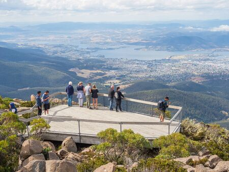 TASMANIA, AUSTRALIA - FEBRUARY 16, 2019: Tourists on a viewing platform on top of Mount Wellington, looking at Hobart, the capital city of Tasmania in Australia.