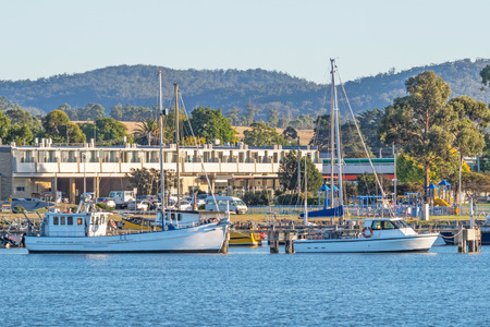 Boats moored at a jetty in St Helens on the East Coast of Tasmania in Australia.