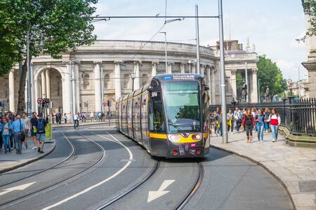 DUBLIN, IRELAND - AUGUST 1, 2019: A modern tram and pedestrians in Dublin, Ireland.