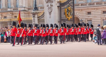 LONDON, UNITED KINGDOM – JULY 11, 2012: Officers and soldiers of the Scots Guards march out of Buckingham Palace during the Changing of the Guard ceremony. Editorial
