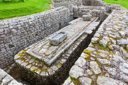 NORTHUMBERLAND, ENGLAND - JULY 7, 2012: The remains of the latrines at Housesteads Roman Fort, part of Hadrian's Wall in Northumberland, England.