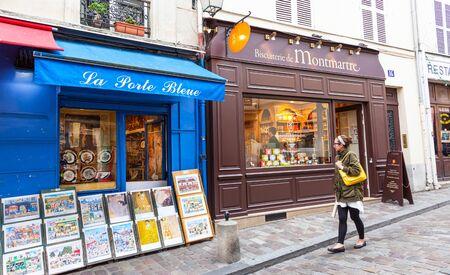 PARIS, FRANCE – JUNE 6, 2012: An unidentified female tourist outside traditional shops in Montmarte in Paris.