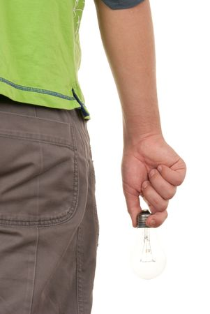Hand holds incandescent lamp behind on white background