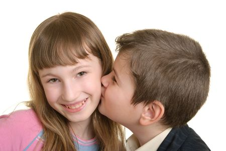 pleasantness: Boy kisses the girl on cheek is isolated on white