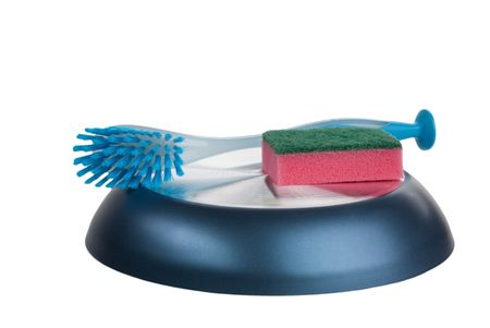 Sponge and brush for ware lie  the turned frying pan isolated in white photo