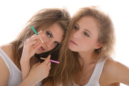 concordance: Two young women with cigarettes isolated in white