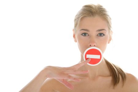 denote: Woman holds prohibiting sign before mouth isolated in white