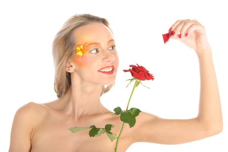 Young woman tears off petals at flower isolated in white photo