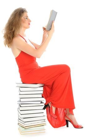 attentiveness: Woman sits on books and reads isolated in white Stock Photo