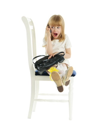 Surprised girl with phone on chair Stock Photo - 8318718