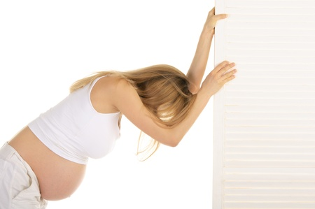 tired pregnant woman leaned on the door Stock Photo