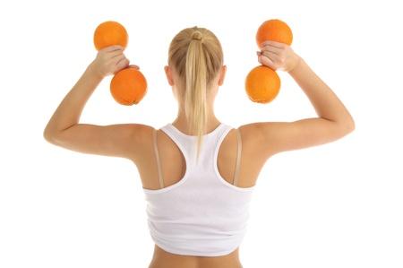 オレンジのフィットネス ダンベルに従事している女性