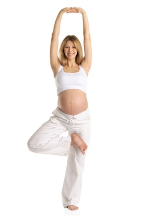 Pregnant woman practicing yoga, standing photo