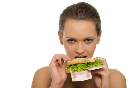 Woman biting a sandwich out of money and lettuce isolated on white photo